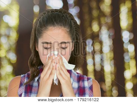 Digital composite of Young woman with hayfever blowing nose in forest trees