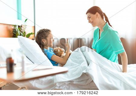 Cute Little Girl Lying In Hospital Bed With Teddy Bear And Talking With Smiling Nurse