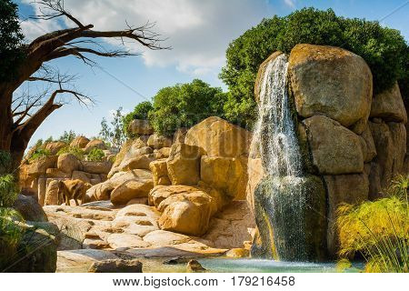 African Landscape With Baobab, Elephants And Waterfall In Animal-friendly Zoo In Valencia, Spain