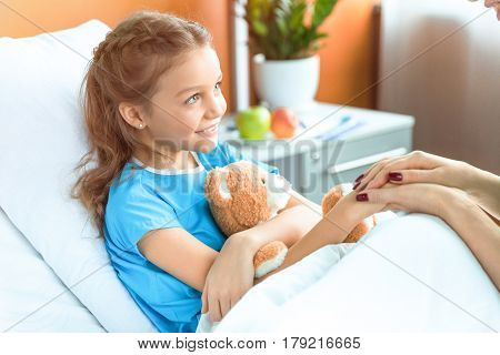 Doctor And Little Patient With Teddy Bear Holding Hands In Hospital