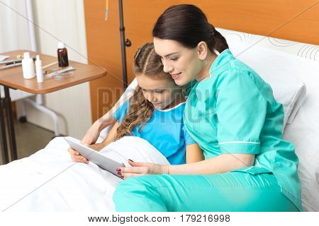 Doctor And Little Girl Using Digital Tablet And Sitting On Bed In Hospital