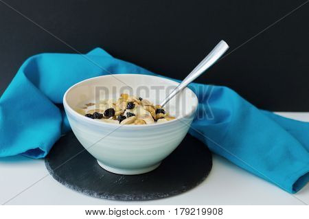 Blue bowl with oatmeal porridge mixed with banana slices nuts and raisin served with a metal spoon on black slate board and blue kitchen towel