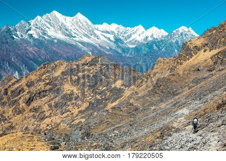 Layered Mountain View grassy Rocks on Foreground and snow capped Peaks on Background and heavy loaded Sherpa Porter walking on Footpath poster