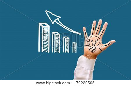 A painted electric light bulb on a man's palm with open fingers with a growing financial profit schedule. A creative idea in business