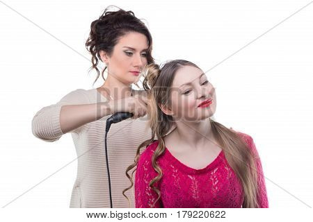 Working hairstylist and blond woman on white background