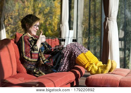 Woman in unusual Clothing Poncho Pants and yellow woollen socks working on portable Computer and making OK hand sign