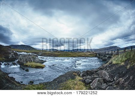 Mountain river in the severe gloomy Icelandic landscape. Stones and moss in the foreground. The picture was taken in cloudy cloudy weather in the autumn afternoon. The picture shows a bridge across the river