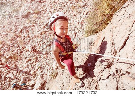 Little Girl Child in protective Helmet training Rock climbing on natural outdoor Wall with belay Rope fixed to Harness top View high above Ground