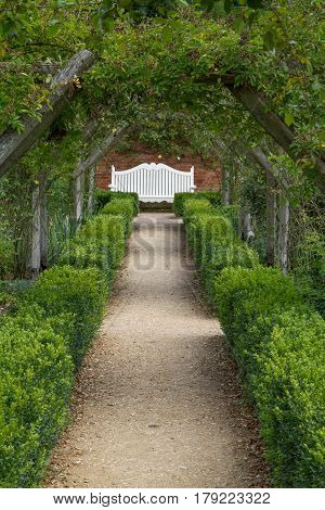 Manicured garden path ledaing to a white bench