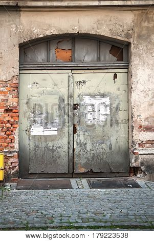 Old wooden arched door with grunge broken brick wall plaster where windows patched with plywood