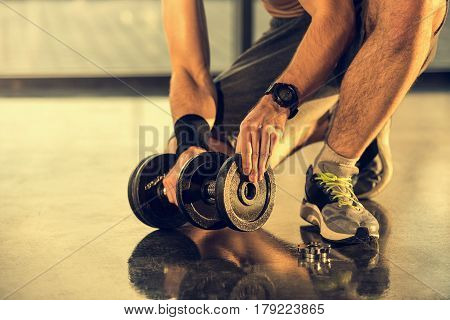 Cropped Shot Of Sportsman Putting Weight On Dumbbell In Gym