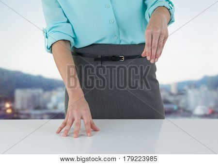 Digital composite of Business woman mid section at desk against blurry skyline