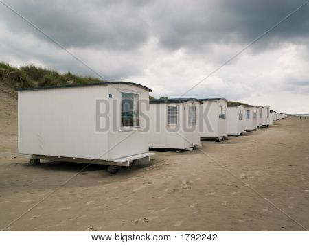 Row of small white houses on the beach of Blokhus Denmark. poster