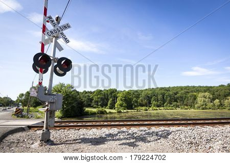 Railroad crossing gate in the upright position allowing vehicle traffic through.