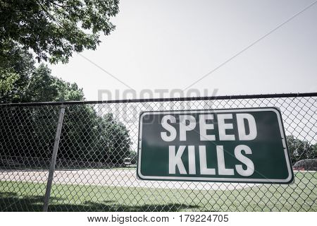 A green and white metal Speed Kills warning sign hangs from the fence of a baseball field to alert passing motorists, de-saturated filter effect.