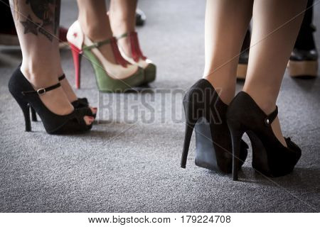 Close up low angle view of three sets of high-heeled shoes worn by a group of women standing together.