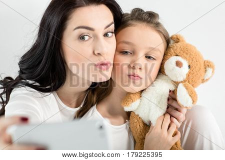 Beautiful Mother And Daughter With Teddy Bear Taking Selfie With Smartphone