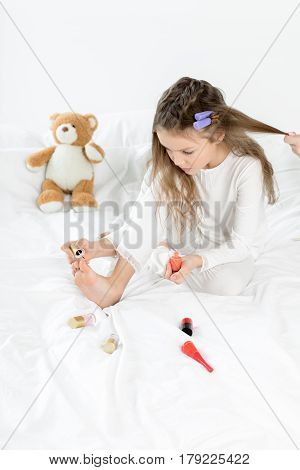 Adorable Little Girl In Pajamas And Curlers Applying Nail Polish To Toenails Sitting On Bed