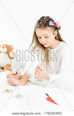 Adorable Little Girl In Pajamas And Curlers Applying Nail Polish To Toenails