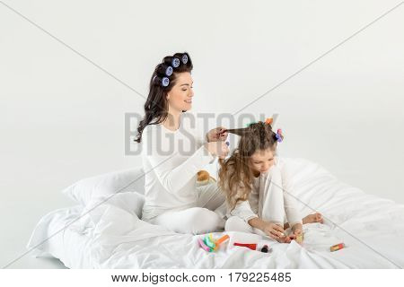 Happy Mother Curling Hair To Daughter Applying Nail Polish While Sitting On Bed