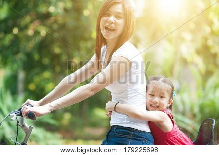 Mother and daughter riding bicycle in the park, Asian family outdoor fun activity.