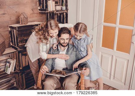 Daughter, Mother And Father Sitting In Rocking Chair And Reading Book