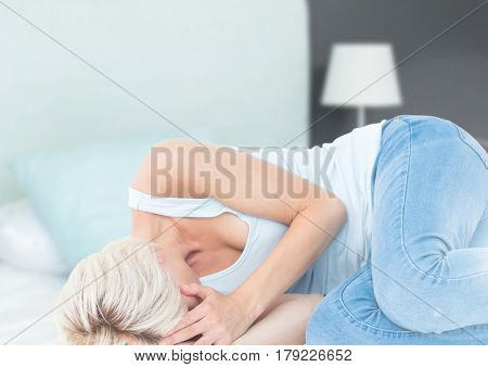 Digital composite of Sad woman crying on bed in bedroom