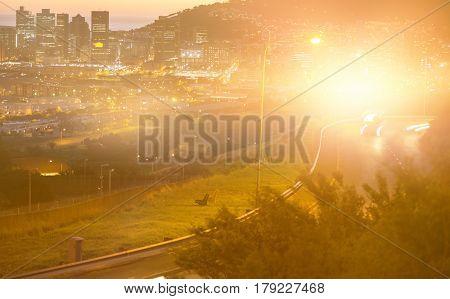 Blurry animated flare against illuminated city street against cityscape