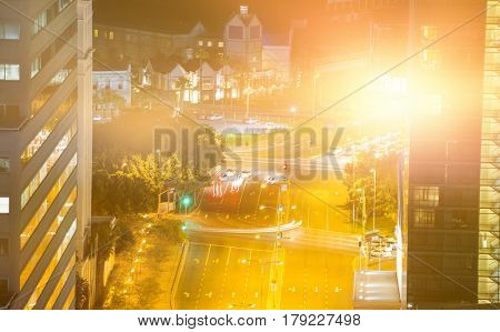 Blurry animated flare against illuminated road amidst building at night