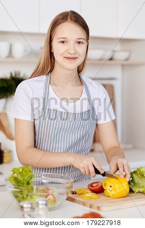Brighten your life. Cheeful content teenage girl cutting vegetables and cooking salad while standing in the kitchen
