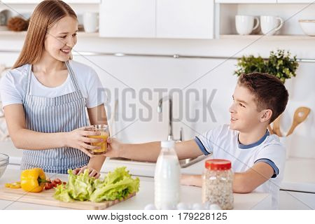 Daily doze of vitamins. Joyful delighted smiling siblings holding glass of juice and having a healthy breakfast while standing in the kitchen