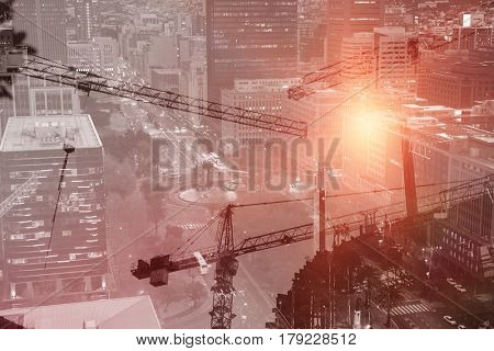 Crane and building construction site against glowing roads by building in city