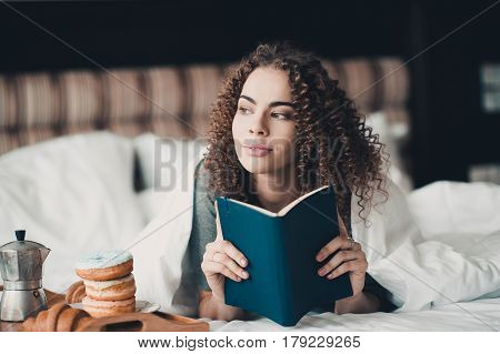 Beautiful girl 24-29 year old reading book in bed with breakfast on wooden tray in hotel room. Good morning. Looking at camera. Leisure activity.
