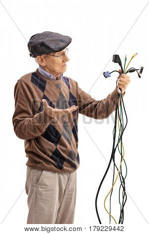 Confused senior looking at electronic cables isolated on white background