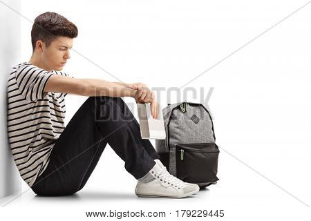 Pensive teen student sitting on the floor and leaning against a wall isolated on white background
