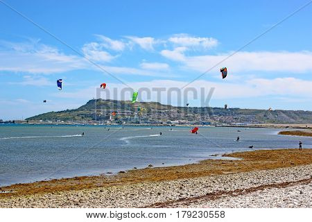 kitesurfers riding their boards in Portland harbour