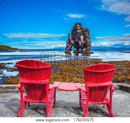 Magic Rock Hvitsercur at sunset. Pair of comfortable red deck chairs set in front of natural wonder. Northern coast of Iceland. Concept of extreme northern tourism