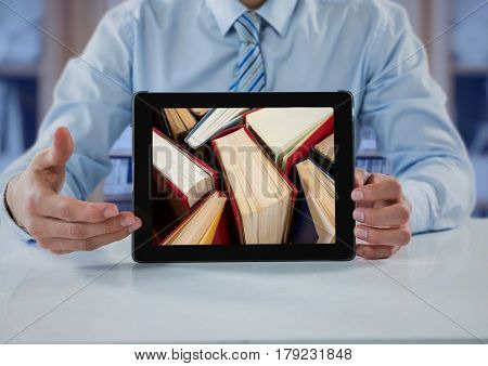 Digital composite of Business man at table with tablet showing standing books against blurry bookshelf with blue overlay