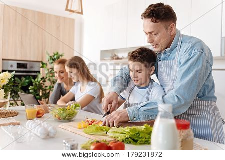 Family cook. Cheerful carign father teaching his son to cook and standing in the kitchen while spending free time together