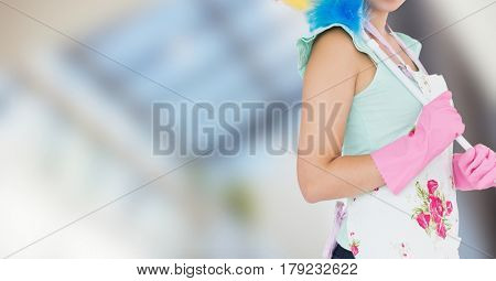 Digital composite of Woman in apron with duster against blurry window