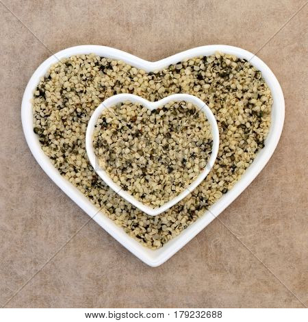 Hulled hemp seed super food in a heart shaped dish on natural hemp paper background.