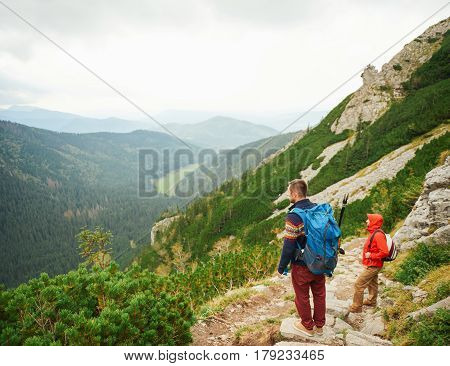 Two young men in hiking gear wearing backpacks looking at the view while walking together along a trail on a rugged mountain range