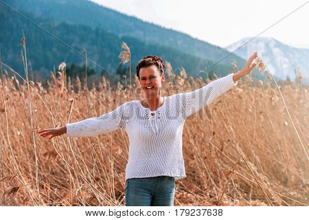 Casual woman mid-fifties happy in the spring in the reeds - landscape