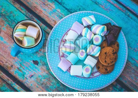 Different kinds of marshmallow cookies and chocolate on blue plate and cup of coffee. Photo toned with vignette