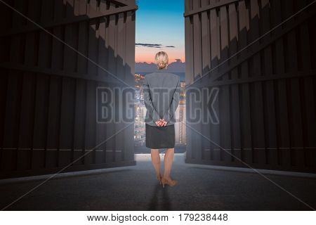 Businesswoman standing with hands behind back against illuminated buildings in city against sky 3d