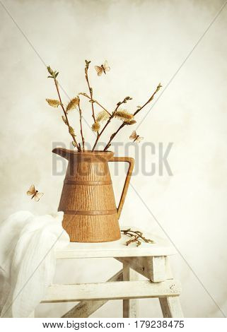 Spring still life with jug of catkin sprigs on step ladder