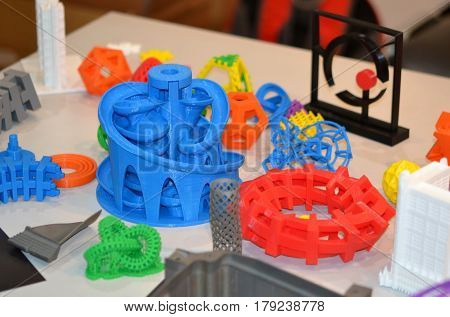 Forms printed by 3d printer. Bright colorful objects printed on a 3d printer on a table