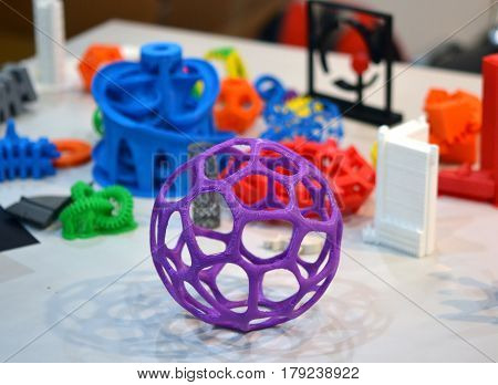 shape printed by 3d printer. Bright colorful objects printed on a 3d printer on a table