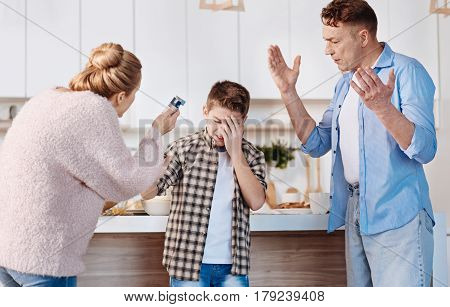 Its unhealthy. Caring parents punishing his son for smoking and giving instructions while standing in the kitchen