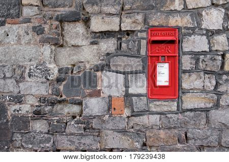 WINDSOR UK - MARCH 18: A traditional iconic British post box in a stone wall in March 2017..